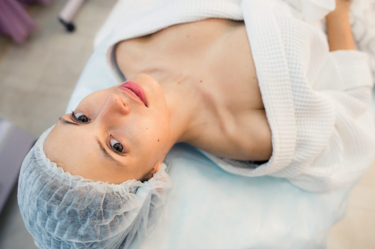 beautiful patient woman smile lying on bed in surgery room hospital