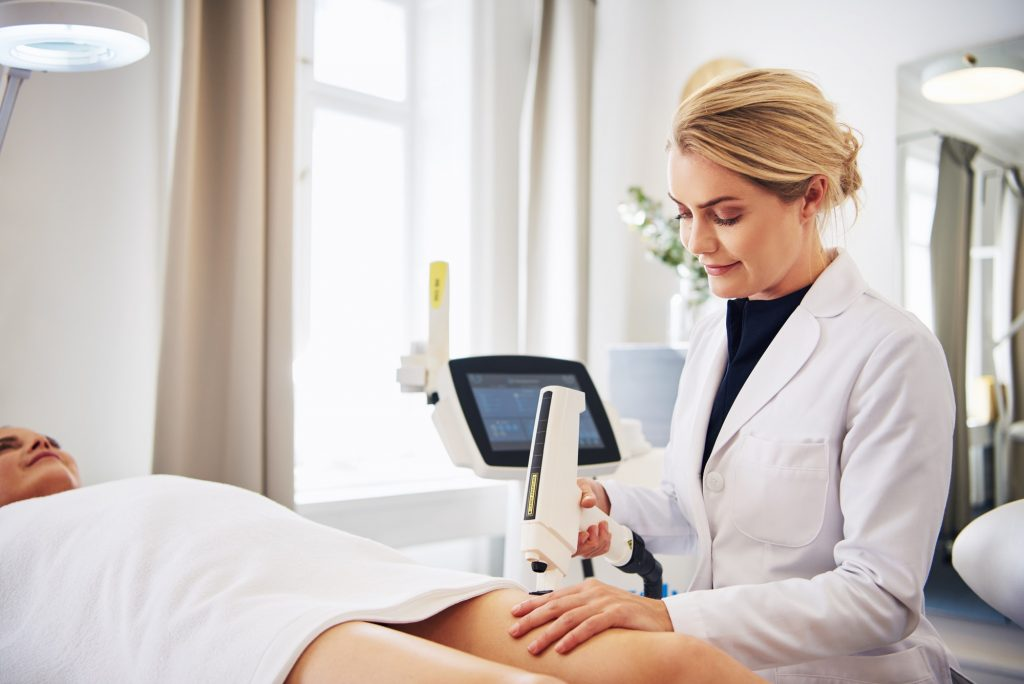 Clinic technician performing laser hair removal on a client's leg
