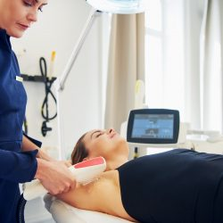 Beautician performing laser hair removal on a female client